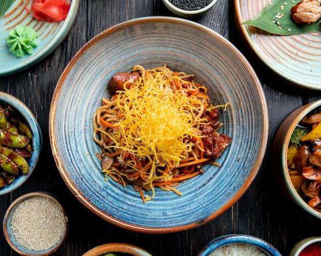 Bovenaanzicht van roergebakken noedels met rundvlees en groenten in een plaat op houten tafel