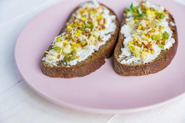 Bovenaanzicht van roggebrood sandwiches met roomkaas en gekiemde bonen, walnoot, zonnebloem en vlas. raw food dieet.