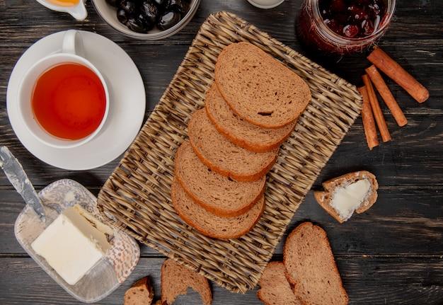 Bovenaanzicht van roggebrood segmenten in mand plaat met kopje thee boter mes kaneel olijven jam op houten tafel