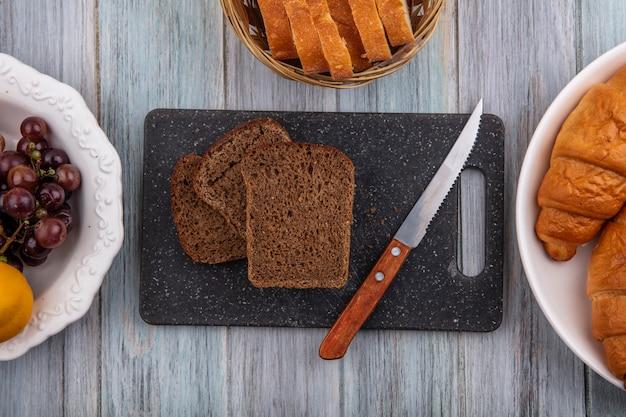 Bovenaanzicht van roggebrood sneetjes en mes op snijplank met croissant druif nectacot op houten achtergrond