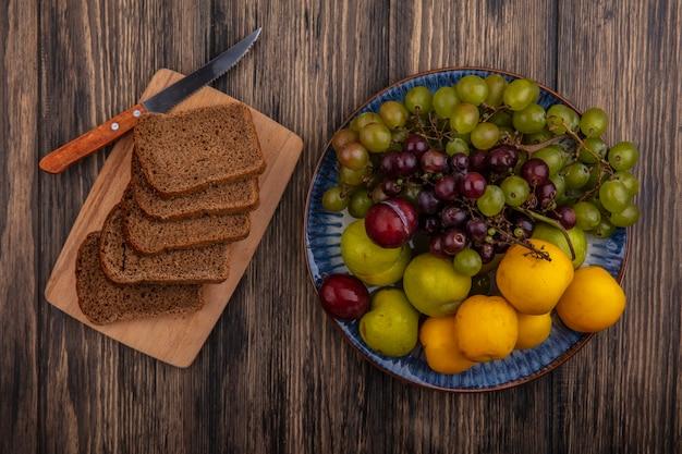 Bovenaanzicht van roggebrood sneetjes en mes op snijplank met mandje van druiven nectacots pluots op houten achtergrond