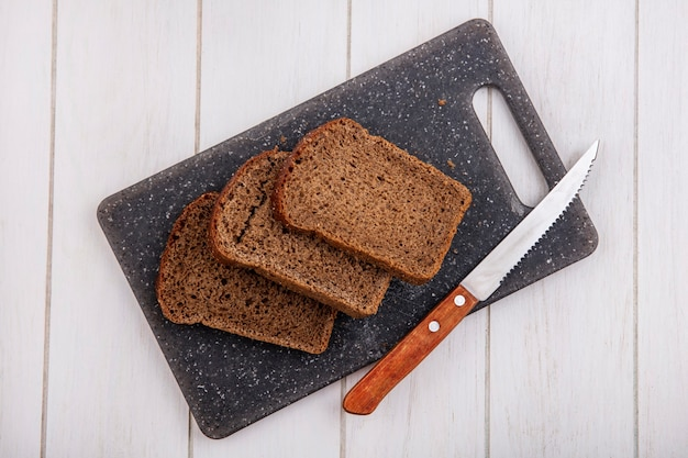 Bovenaanzicht van roggebrood sneetjes en mes op snijplank op houten achtergrond