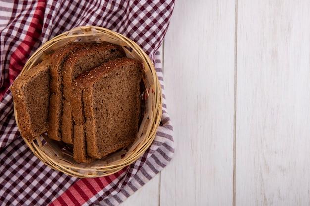 Bovenaanzicht van roggebrood sneetjes in mand op geruite doek op houten achtergrond met kopie ruimte
