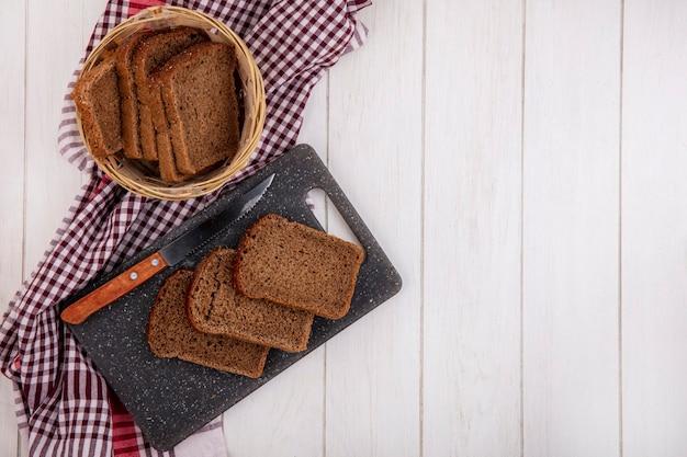 Bovenaanzicht van roggebrood sneetjes met mes op snijplank en in mand op geruite doek op houten achtergrond met kopie ruimte