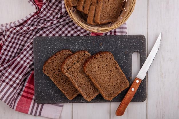 Bovenaanzicht van roggebrood sneetjes met mes op snijplank en in mand op geruite doek op houten achtergrond
