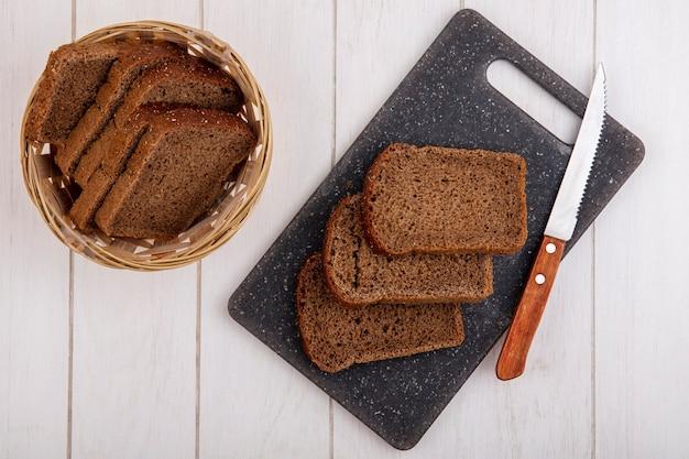 Bovenaanzicht van roggebrood sneetjes met mes op snijplank en in mand op houten achtergrond