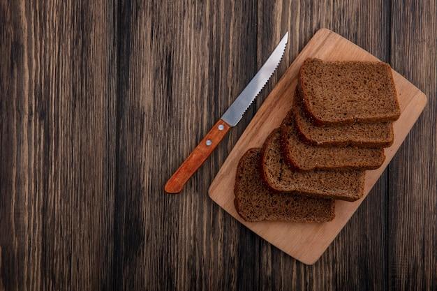 Bovenaanzicht van roggebrood sneetjes op snijplank en mes op houten achtergrond met kopie ruimte