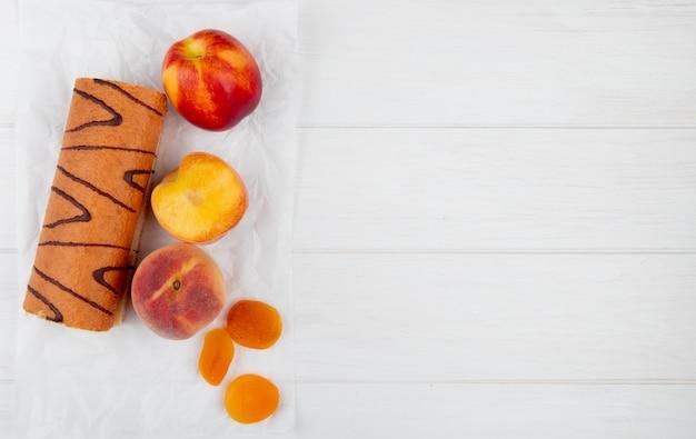 Bovenaanzicht van roll cake met verse perziken en gedroogde abrikozen op wit met kopie ruimte
