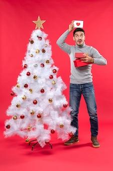 Bovenaanzicht van romantische volwassene in een grijze blouse staande in de buurt van de versierde witte kerstboom