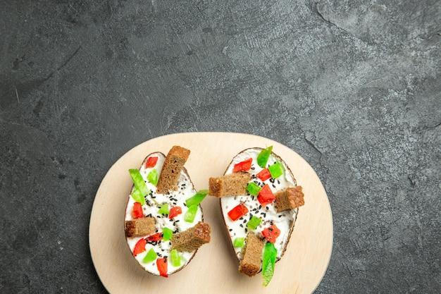 Bovenaanzicht van romige avocado's met gesneden paprika en stukjes brood op grijze ondergrond