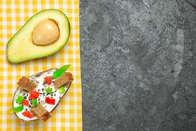 Bovenaanzicht van romige avocado's met verse avocado op grijze ondergrond