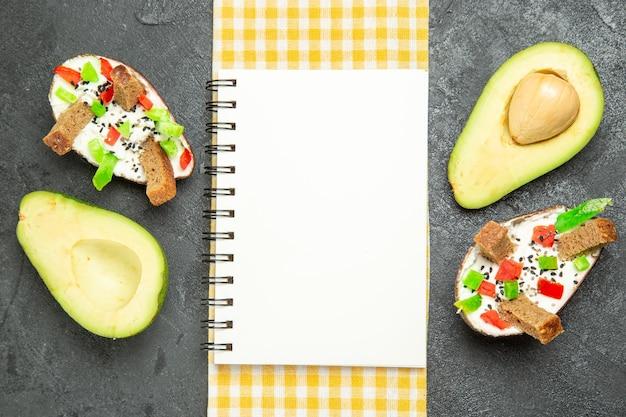 Bovenaanzicht van romige avocado's met verse avocado's op donkergrijs oppervlak