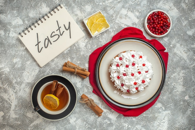 Bovenaanzicht van romige cake versierd met fruit op een rode doek