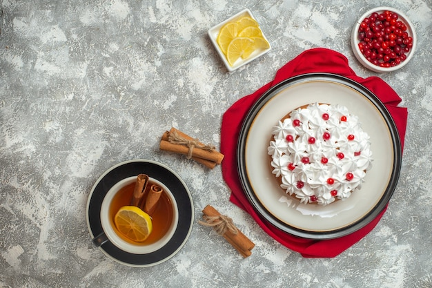 Bovenaanzicht van romige cake versierd met fruit op een rode handdoek en een kopje zwarte thee met kaneellimoenen