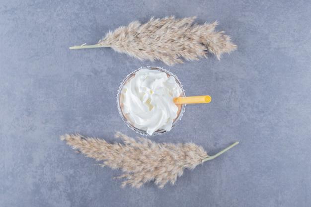 Bovenaanzicht van romige milkshake op grijze achtergrond.