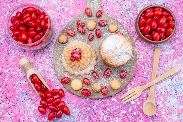 Bovenaanzicht van romige sandwichkoekjes heerlijk met rode verse kornoeljes op heldere, koekjescake biscuit zure fruitbes