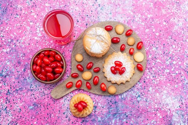 Bovenaanzicht van romige sandwichkoekjes met kornoeljessap van rode kornoeljes op heldere, koekjescake biscuit zoetzure fruitbes