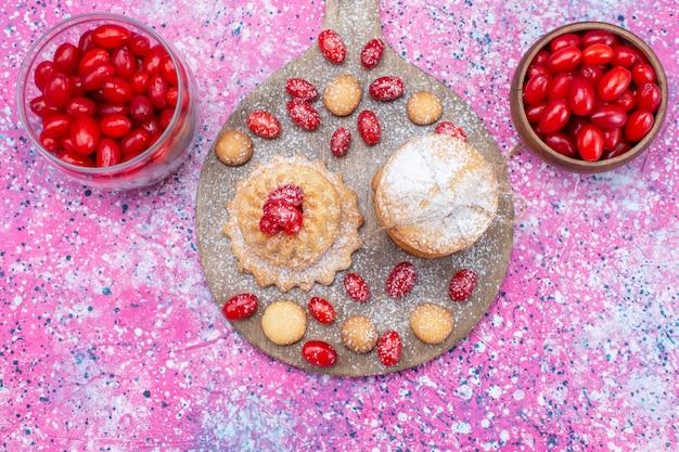 Bovenaanzicht van romige sandwichkoekjes met rode verse kornoeljes op heldere, koekjescake biscuit zoetzure fruitbes