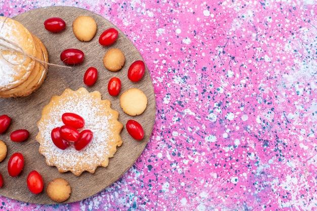 Bovenaanzicht van romige sandwichkoekjes met verse en zure rode kornoeljes op heldere, koekjescake biscuit zoetzure fruitbes
