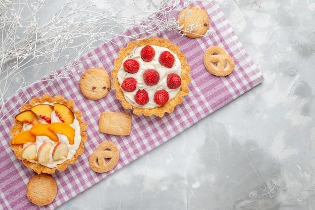 Bovenaanzicht van romige taarten met witte lekkere room en gesneden aardbeien perziken abrikozen met koekjes op licht bureau, fruit cake room bakken