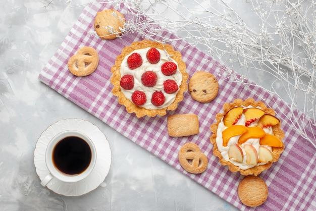 Bovenaanzicht van romige taarten met witte lekkere room en gesneden aardbeien perziken abrikozen met koekjes op licht bureau, fruitcake crème bak thee