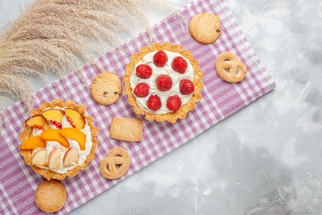Bovenaanzicht van romige taarten met witte lekkere room en gesneden aardbeien perziken abrikozen met koekjes op licht bureau, fruitcake room bakken