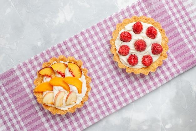 Bovenaanzicht van romige taarten met witte lekkere room en gesneden aardbeien perziken abrikozen op licht bureau, fruitcake room bakken