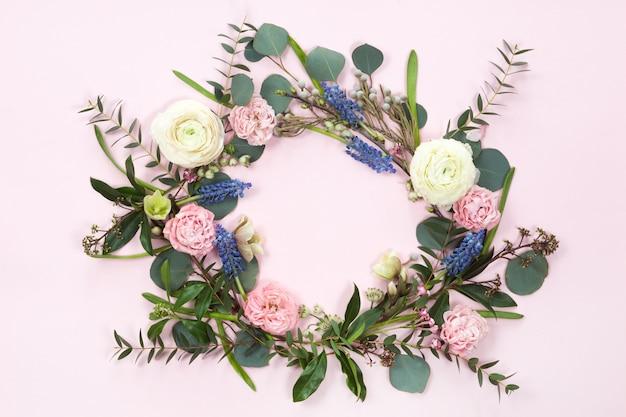 Bovenaanzicht van ronde bloem frame krans met rozen, ranunculus, bladeren, knoppen, takken geïsoleerd op een witte achtergrond