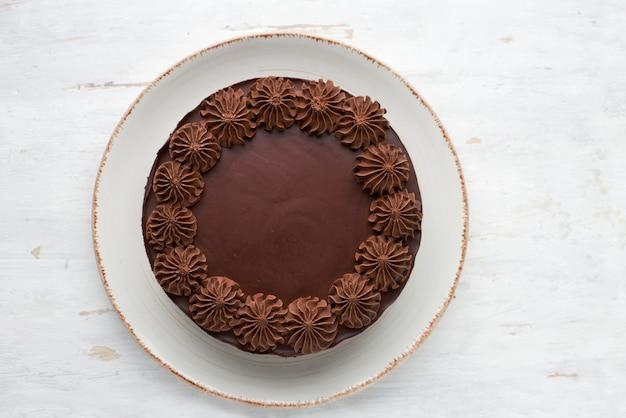 Bovenaanzicht van ronde gebakken chocoladetaart op een lichte houten ondergrond.