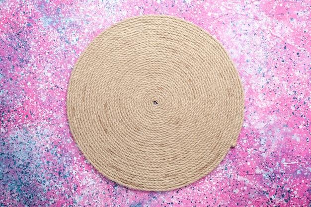 Bovenaanzicht van ronde gevormde touwen op roze oppervlak