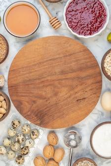 Bovenaanzicht van ronde houten plank onder meel jam honing eieren bruine rijst op ijs achtergrond