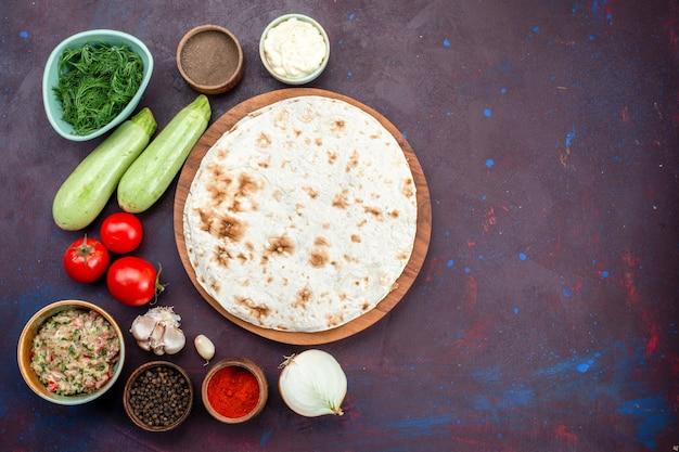 Bovenaanzicht van ronde pitabroodje met greens verse groenten en kruiden op donkere ondergrond