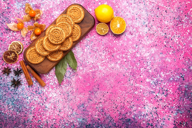 Bovenaanzicht van ronde zoete koekjes bekleed met kaneel en citroen op roze ondergrond