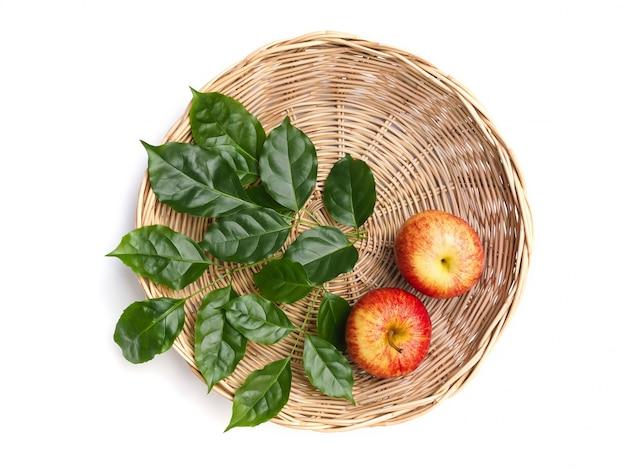 Bovenaanzicht van rood fruit appels in bamboe manden en groene bladeren geïsoleerd op een witte ruimte met uitknippad