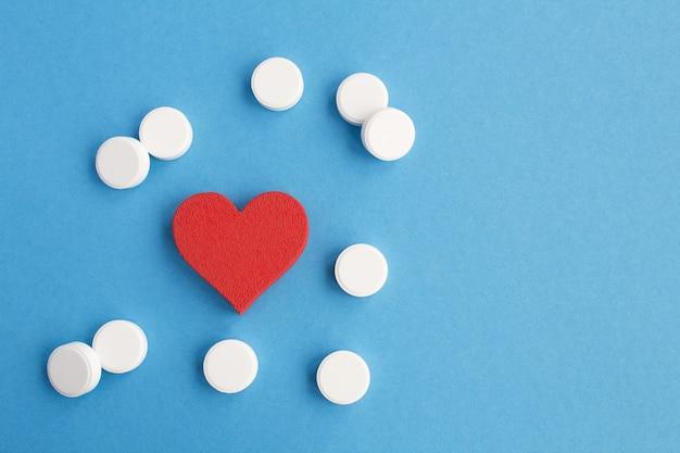 Bovenaanzicht van rood hart en witte pillen op blauwe ondergrond