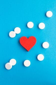 Bovenaanzicht van rood hart en witte pillen op het blauw