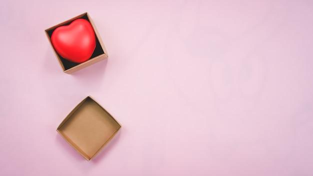 Bovenaanzicht van rood hart in de bruine doos van papier