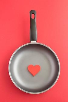 Bovenaanzicht van rood hart in een koekenpan op rood. locatie verticaal.
