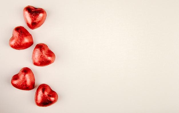 Bovenaanzicht van rood hartvormige snoepjes geïsoleerd op een witte tafel met kopie ruimte