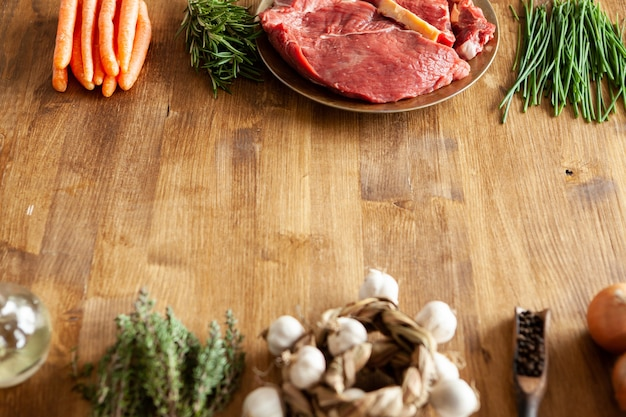 Bovenaanzicht van rood vlees in een vintage bord naast groene ui. exemplaarruimte beschikbaar.