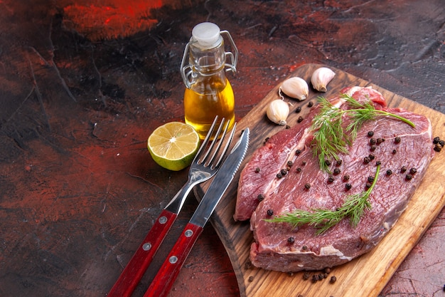Bovenaanzicht van rood vlees op houten snijplank en knoflook groene peper oi fles vork en mes op donkere achtergrond