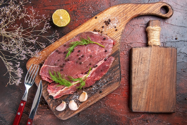 Bovenaanzicht van rood vlees op houten snijplank knoflook vork en mes op donkere achtergrond