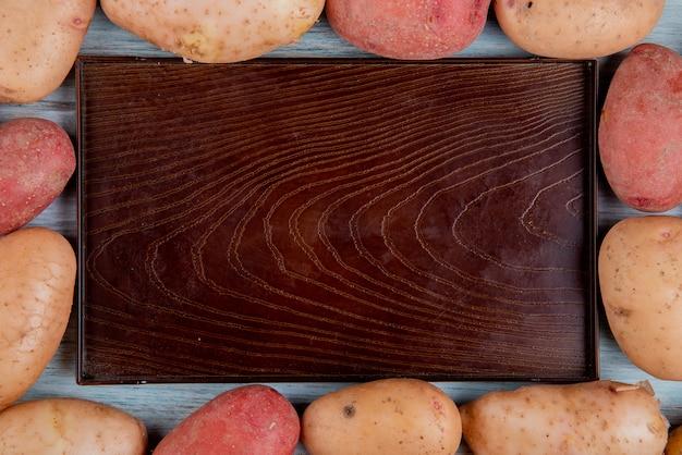 Bovenaanzicht van roodbruin en rode aardappelen in vierkante vorm rond lege lade op hout