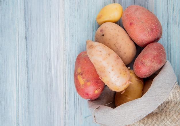 Bovenaanzicht van roodbruine rode en nieuwe aardappelen morsen uit zak op houten oppervlak met kopie ruimte