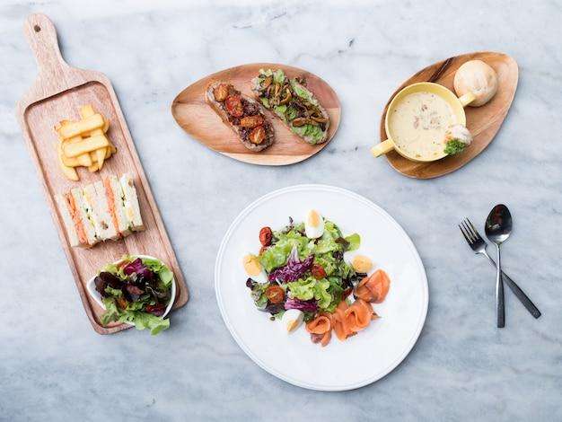 Bovenaanzicht van rook zalm salade met soep en club sanwich op tafel.