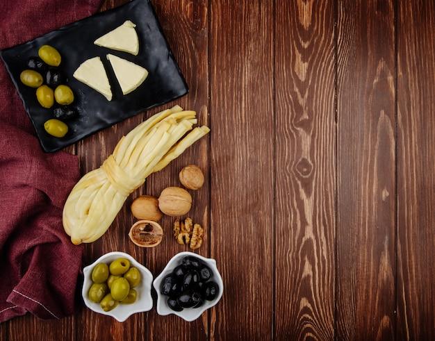 Bovenaanzicht van roomkaas in driehoekige vorm met ingelegde olijven op een zwart dienblad en walnoten met string kaas op donkere houten tafel met kopie ruimte