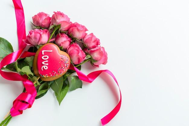 Bovenaanzicht van roos boeket met cookie