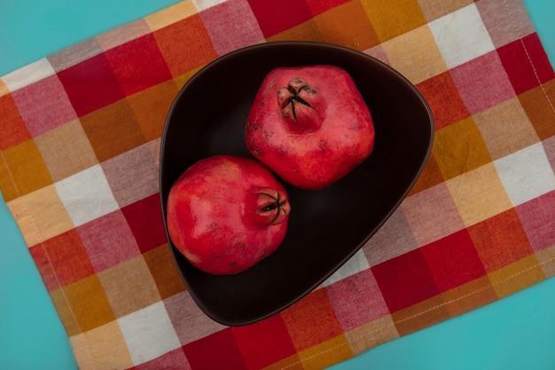 Bovenaanzicht van rossige verse granaatappels op een kom op een gecontroleerde doek op een blauwe achtergrond
