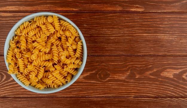Bovenaanzicht van rotini pasta in kom op houten oppervlak met kopie ruimte