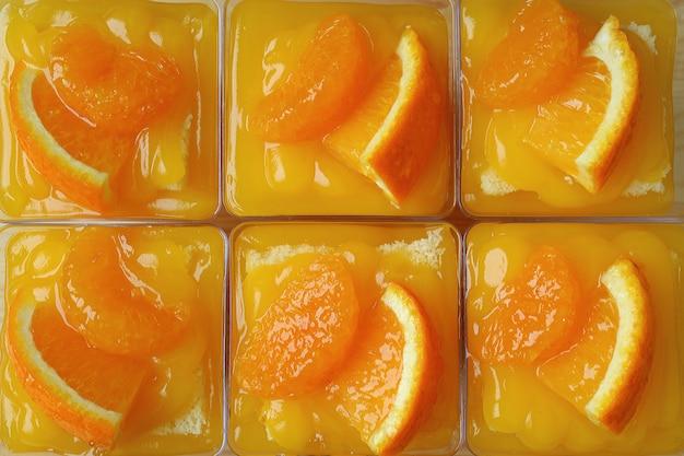 Bovenaanzicht van rowed-up mandarijn-oranje taarten gegarneerd met verse sinaasappelen in glazen kommen